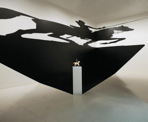Silveira Regina: A szent paradoxona 1994, (installáció, posztamens, fafigura, öntapadós vinilkivágás, árnykép-sziluett): Regina Silveira és MAC/USP Collection Museum of Contemporary Art / University of Sao Paulo gyűjteménye. Fotó: Mauro Restiffe